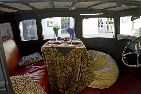 Car in front of restaurant, set up for dining inside